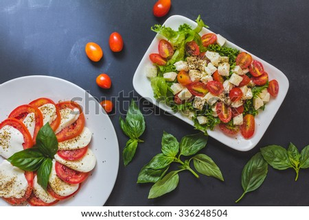 Caprese salad, Italian salad,Tomato mozzarella basil leaves. Top view on black background - stock photo