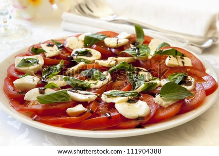 Caprese salad on a serving platter.  Tomatoes with baby mozzarella, basil, and a balsamic dressing. - stock photo