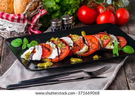 Caprese Salad on black plate - Salad with Tomatoes, Mozzarella Cheese, Basil and Balsamic. Salad Dressing with Pesto Sauce - stock photo