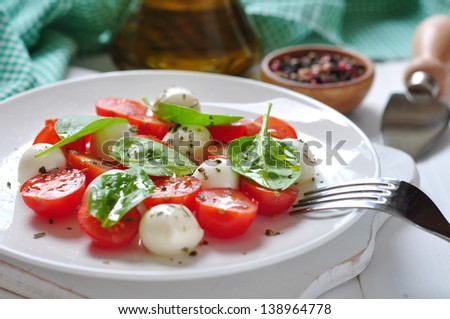Caprese Salad on white plate closeup. Small shallow DOF.
