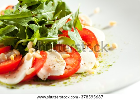 Caprese Salad - Salad with Tomatoes, Mozzarella Cheese and Rocket Salad. Salad Dressing with Pesto Sauce and Pine Nuts