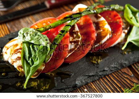Caprese Salad - Salad with Tomatoes, Mozzarella Cheese, Basil, Asparagus and Balsamic. Salad Dressing with Pesto Sauce - stock photo