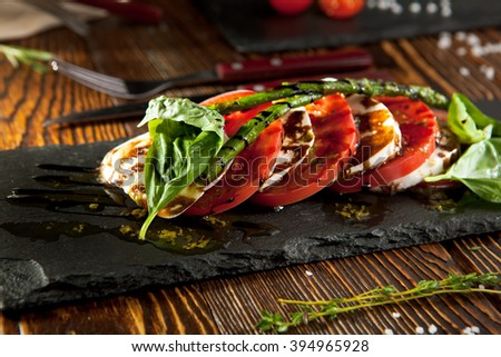Caprese Salad - Salad with Tomatoes, Mozzarella Cheese, Basil, Asparagus and Balsamic. Salad Dressing with Pesto Sauce - stock photo