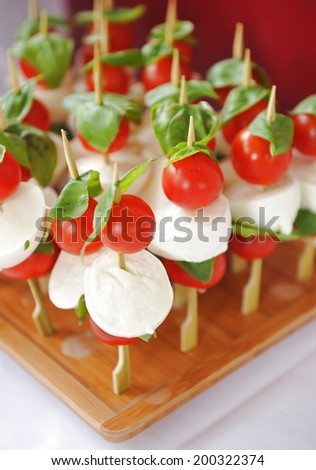 Caprese salad. Skewers with tomato and mozzarella with basil.  - stock photo