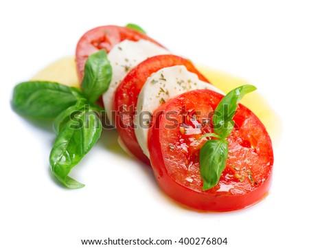 Caprese Salad. Tomato and Mozzarella slices with basil leaves. Isolated on white background - stock photo
