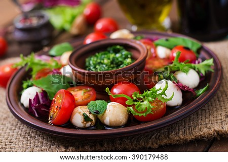 Caprese salad tomato and mozzarella with basil and herbs on a brown plate - stock photo