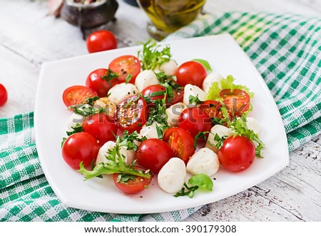 Caprese salad tomato and mozzarella with basil and herbs on a white plate