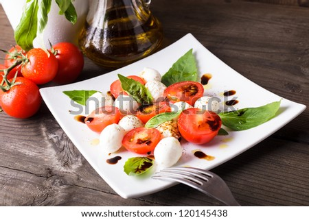 Caprese salad: tomato, mozzarella, basil leaves with olive oil and balsamico - stock photo