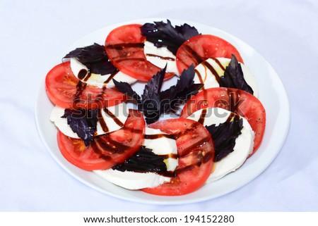 Caprese Salad (Tomato mozzarella salad) with balsamic glaze  - stock photo