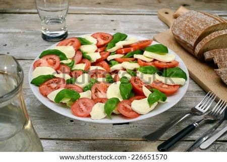 Caprese salad (tomatoes, mozzarella, basil leaves & olive oil ) on white plate & vintage wooden desk - stock photo