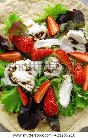 Caprese salad with fresh lettuce, mozzarella cheese and strawberries. with flatread. healthy summer snack. comfort street food - stock photo