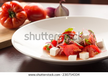 Caprese salad with ingredients on wooden table - stock photo