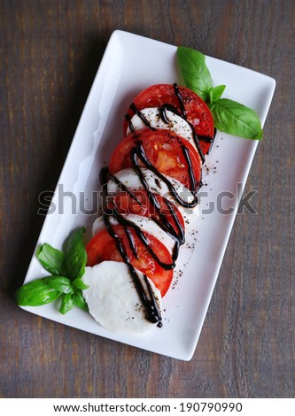 Caprese salad with mozarella cheese, tomatoes and basil on plate, on wooden table background - stock photo
