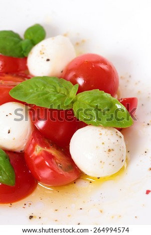 Caprese salad with mozzarella, cherry tomatoes and basil leaves