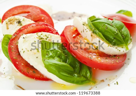 Caprese salad with mozzarella, tomato, basil and balsamic vinegar arranged on white plate - stock photo