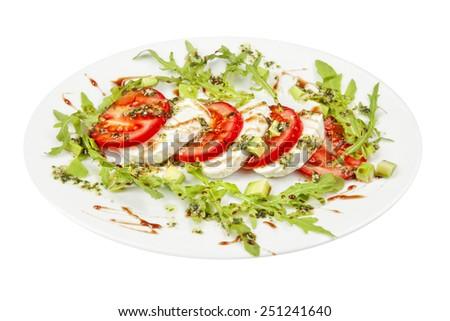 Caprese salad with mozzarella, tomato, basil and balsamic vinegar arranged on white plate - stock photo