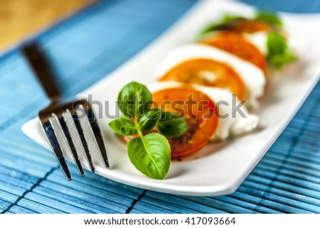 caprese salad with silver fork and blue mat on wooden background