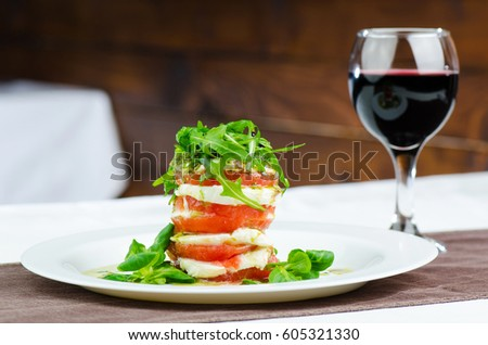 Caprese Salad With Tomato And Mozzarella Cheese Next To Glass Of Red Wine