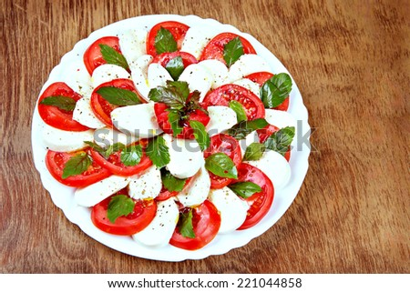 Caprese salad with tomatoes and mozzarella on the plate - stock photo