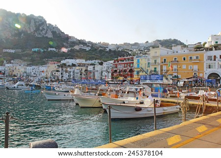 CAPRI, ITALY - OCTOBER 10 2014: Tour boat operators and buildings at Marina Grande on the island of Capri. Boats leaving from pier 0 provide tours all over the island including the famous Blue Grotto. - stock photo