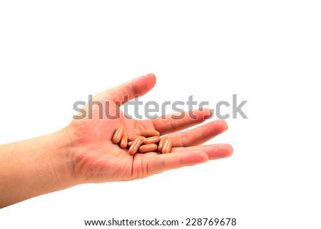 Capsule on holding hand isolated on white - stock photo