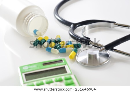Capsule Pills Spill out From Bottle with Stethoscope and Calculator on White Background, Medical Care Cost Concept and Selective Focus  - stock photo