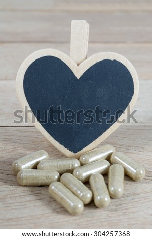 Capsule pills  with blank heart shape blackboard on wood background