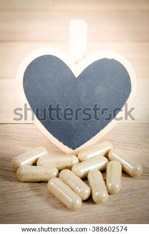 Capsule pills with blank heart shape blackboard on wood background - stock photo