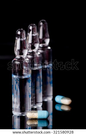 Capsules and ampules on black background with reflection
