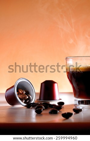 capsules and cup of hot espresso coffee on a table and brown background close up - stock photo