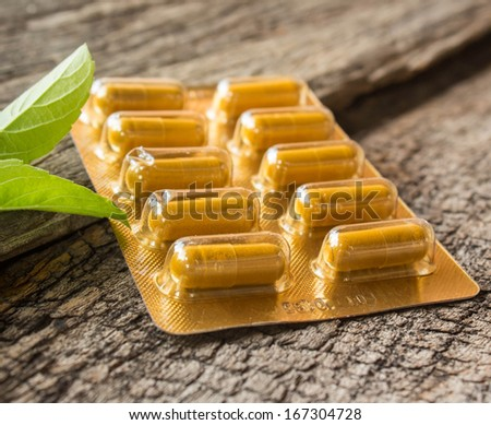 capsules and pills closeup on old wood. - stock photo