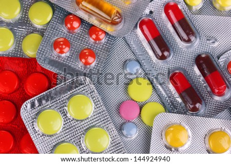 Capsules and pills packed in blisters close-up background - stock photo