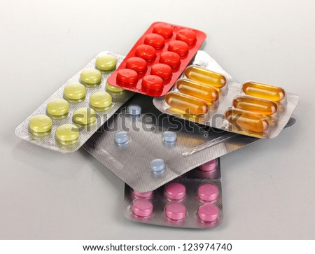 Capsules and pills packed in blisters isolated on white - stock photo