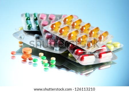 Capsules and pills packed in blisters, on blue background - stock photo