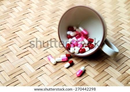 capsules are pouring from coffee cup in soft focus and vintage tone - stock photo