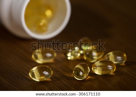 Capsules of fish oil spilled out open container on wooden table. Macro. - stock photo