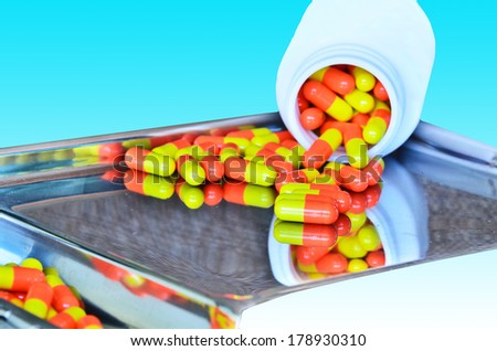 capsules on pill counting tray on blue white background