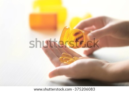 Capsules spilled from orange pill bottle to woman hand, blurred