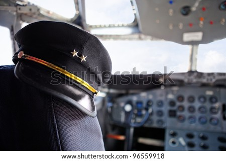 Captain pilot hat inside an airplane cabin - stock photo