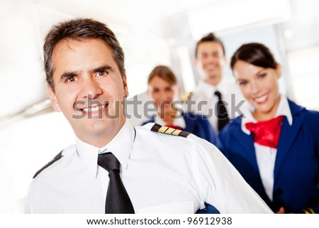 Captain with cabin crew in an airplane smiling - stock photo