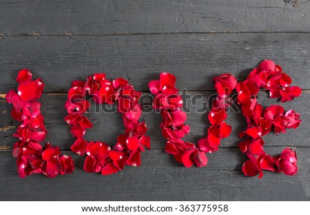 Caption word love on black wood background. Love inscription from the petals of roses.
