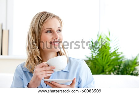 Captivating businesswoman holding a cup sitting on a sofa at home - stock photo
