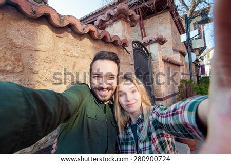Capturing a happy moment. Beautiful young multi ethnic couple bonding to each other and smiling while making selfie with old town sightseeing in the background. - stock photo