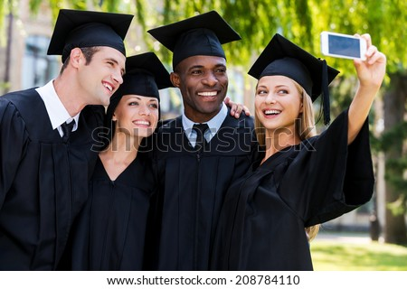 Capturing a happy moment. Four college graduates in graduation gowns standing close to each other and making selfie