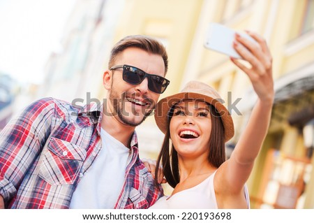 Capturing a happy moment. Low angle view of happy young loving couple making selfie while standing outdoors together  - stock photo