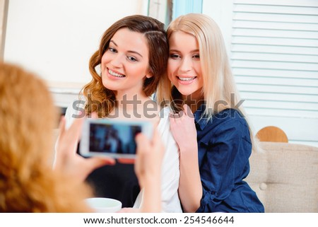 Capturing a happy moment. Three young beautiful female friends sitting in cafe and making photos with their smartphone while drinking coffee - stock photo