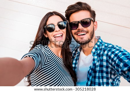Capturing bright moments. Joyful young loving couple making selfie on camera while standing outdoors - stock photo