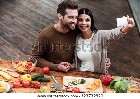 Capturing bright moments together. Top view of beautiful young couple making selfie and smiling while preparing food together - stock photo