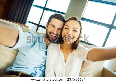 Capturing fun. Beautiful young loving couple bonding to each other and making selfie while sitting on the couch together - stock photo