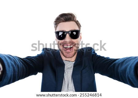 Capturing fun. Cheerful young man in shirt making selfie while standing against white background - stock photo